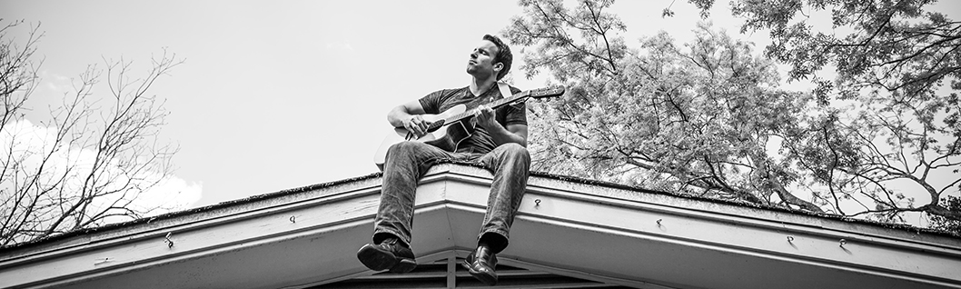 Abel James playing guitar on the roof of his home in Austin, TX.